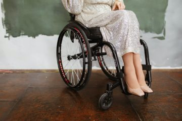 woman in white robe sitting on black wheelchair