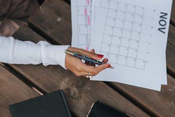 crop woman writing in calendar